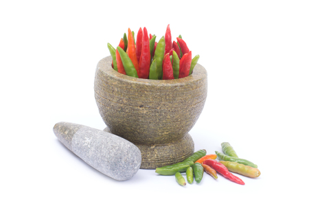 Bird eye chili in stone mortar isolated on white background, bird's chili or Thai chili is a chili pepper, a cultivar from the species Capsicum annuum, commonly found in Southeast Asia.