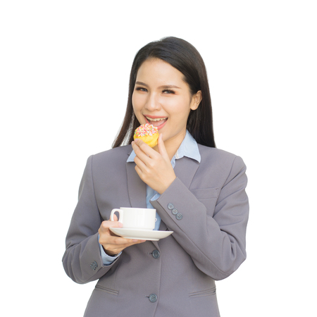 Portrait of business woman with cup of tea or coffee and one hand holding donut isolated on white background Imagens
