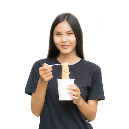 Young beautiful asian woman eating yummy hot and spicy instant noodle using chopsticks isolated on white background.Unhealthy concept