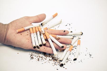 la mano dell'uomo tiene una sigaretta in mano. Al fine di smettere di fumare sigarette crea dipendenza. Concetti di salute e giornata per non fumatori