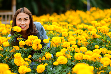 Happy and beautiful young woman relaxing enjoying the fresh beauty of gorgeous orange marigold flowers field in Loei, Thailand 免版税图像