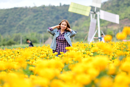 Happy and beautiful young woman relaxing enjoying the fresh beauty of gorgeous orange marigold flowers field in Loei, Thailand Imagens - 122138680