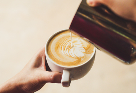 Closeup image of female barista holding and pouring milk for prepare cup of coffee, latte art, vintage color tone, coffee preparation and service concept, lifestyle
