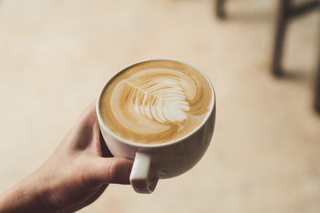 Closeup image of female barista holding latte art coffee