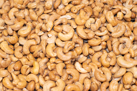 Tasty cashew nuts fried as background, top view 版權商用圖片