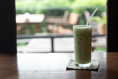 Iced Green tea with a straw on wood table