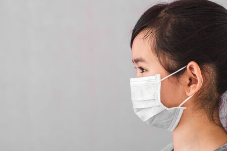 Little asian girl wearing sterile medical mask for protect Covid-19 isolated on gray background. Copy space. Фото со стока