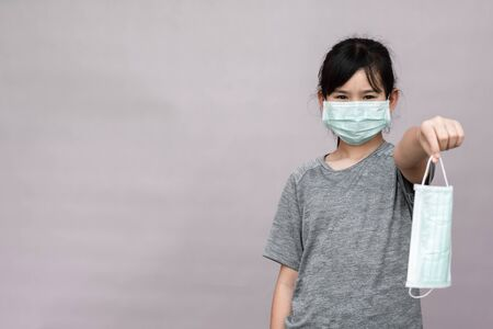 Little girl has sterile medical  mask protect herself from Coronavirus COVID-19 isolated on gray background, child with a mask on her nose for safety outdoor activity, illness or air pollution