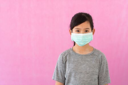 Little asian girl wearing sterile medical mask for protect Covid-19 isolated on pink background. Copy space.