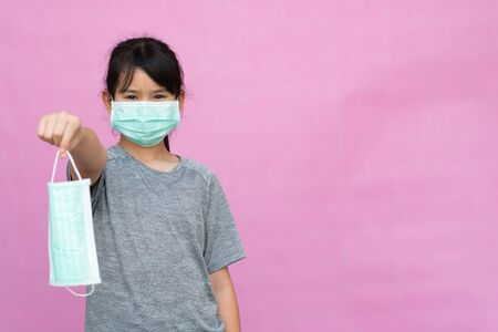 Little girl has sterile medical  mask protect herself from Coronavirus COVID-19 isolated on pink background, child with a mask on her nose for safety outdoor activity, illness or air pollution Фото со стока