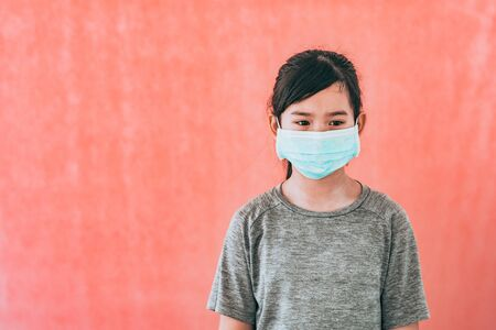 Little asian girl wearing sterile medical mask for protect Covid-19 isolated on red background. Copy space. Фото со стока