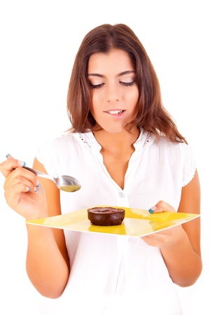 Young woman eating chocolate cake on white background photo