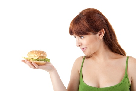 Young attractive woman eating hamburger on white background photo