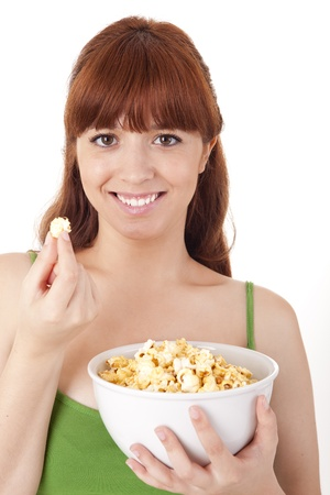 Beautiful woman eating popcorn on white background photo
