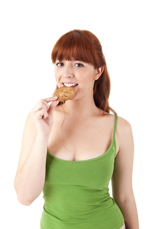 chocolate chip cookies: Beautiful young woman eating diet biscuits on white background Stock Photo