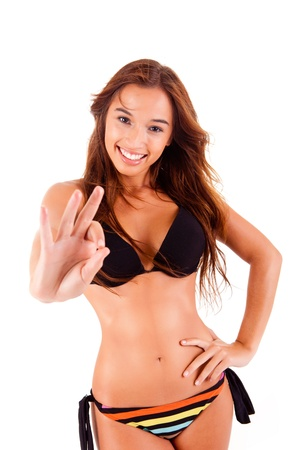 Beautiful bikini woman showing Ok sign on white background photo