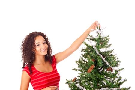 Beautiful african woman decorating Christmas tree Stock Photo - 17300400