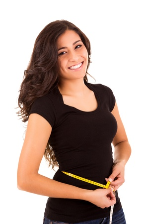 Beautiful slim woman measuring her body with a measuring tape