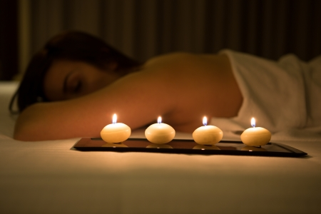 Woman relaxing in spa salon in the dark - Focus on candles photo