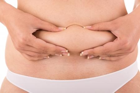 partes del cuerpo humano: Mujer mostrando su grasa corporal Foto de archivo