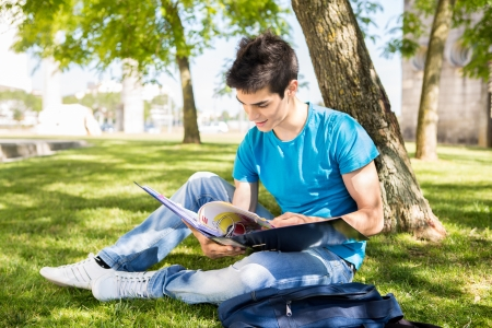 college boy: Young student studying at the school garden Stock Photo