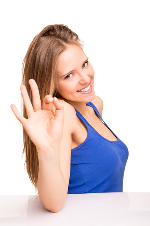Portrait of a smiling woman showing OK sign over white background photo