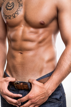 Close-up of the abdominal muscles young athlete over white background