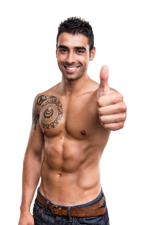 Fit man showing thumbs up over white background Stock Photo