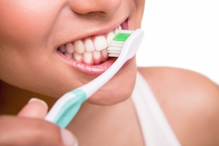 Smiling young woman with healthy teeth holding a tooth brush photo