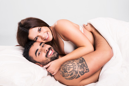 Love couple flirting and hugging in bed photo