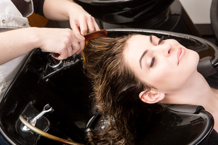 washing hair: Beautiful woman washing her hair in hairsalon