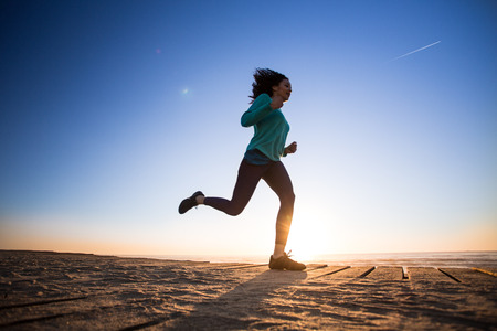 Young afro woman running on the beach photo