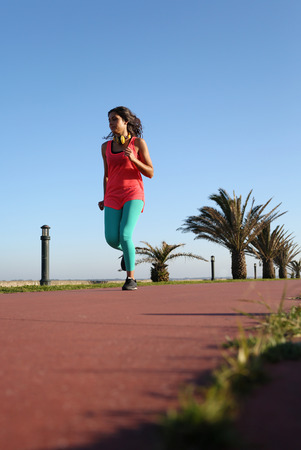 Fit woman running in the city park photo