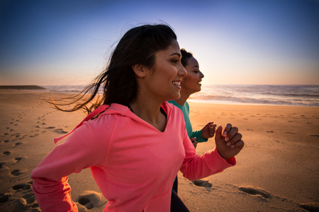 latin american: Couple of women running and walking on the beach