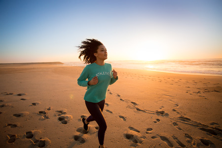 Young afro woman running on the beach Stock Photo