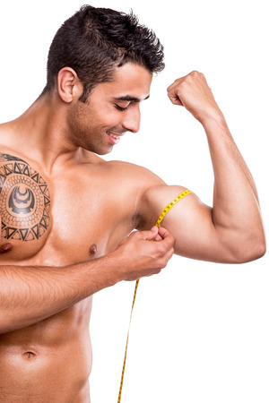 Fitness man measuring his body over white background photo