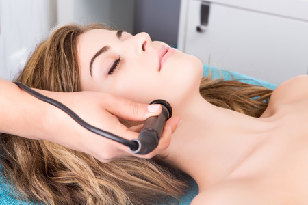 Woman doing cosmetic procedures in spa clinic photo