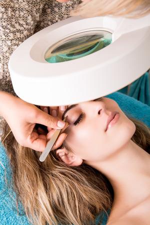 tweezing eyebrow: Woman getting tweezing eyebrow by beautician