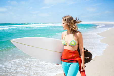 Beautiful surfer girl holding a surfboard on the beach photo
