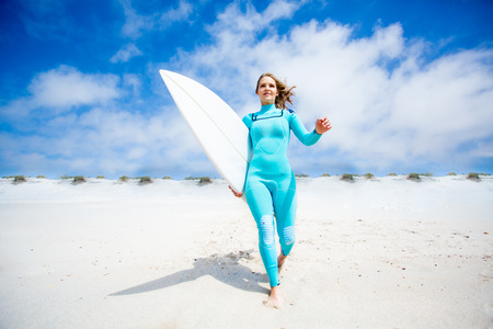 Surfer girl running at the beach with her surfboard photo