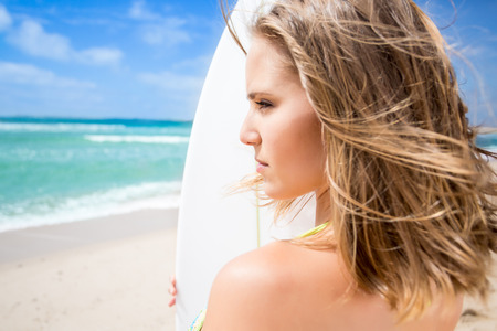 Surfing beautiful woman waiting for the waves on the beach photo