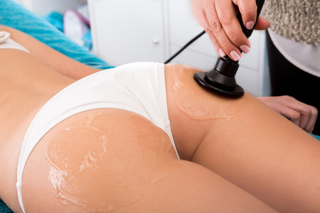 Woman getting anticellulite and anti fat therapy in beauty salon