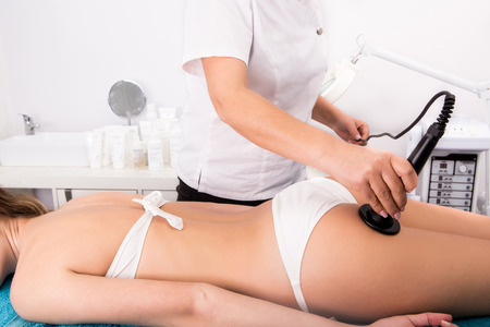 Woman getting anticellulite and anti fat therapy in beauty salon photo