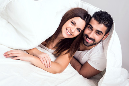 kiss couple: Young couple hugging while lying in bed in the morning Stock Photo