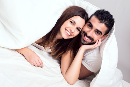 passionate lovers: Young couple hugging while lying in bed in the morning Stock Photo