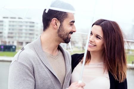 Happy couple under a white umbrella in the city photo