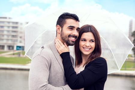 Happy couple under a white umbrella in the city