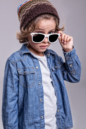 Fashion little boy wearing trendy white sunglasses