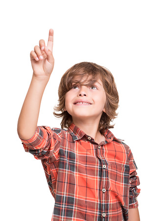 Cool young boy pointing to empty space over white