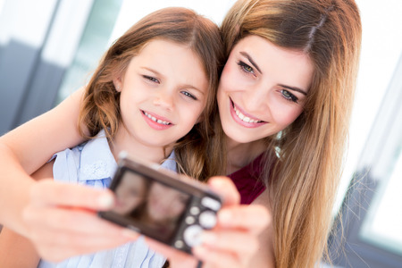 Girl taking a selfie with her mother or sister photo